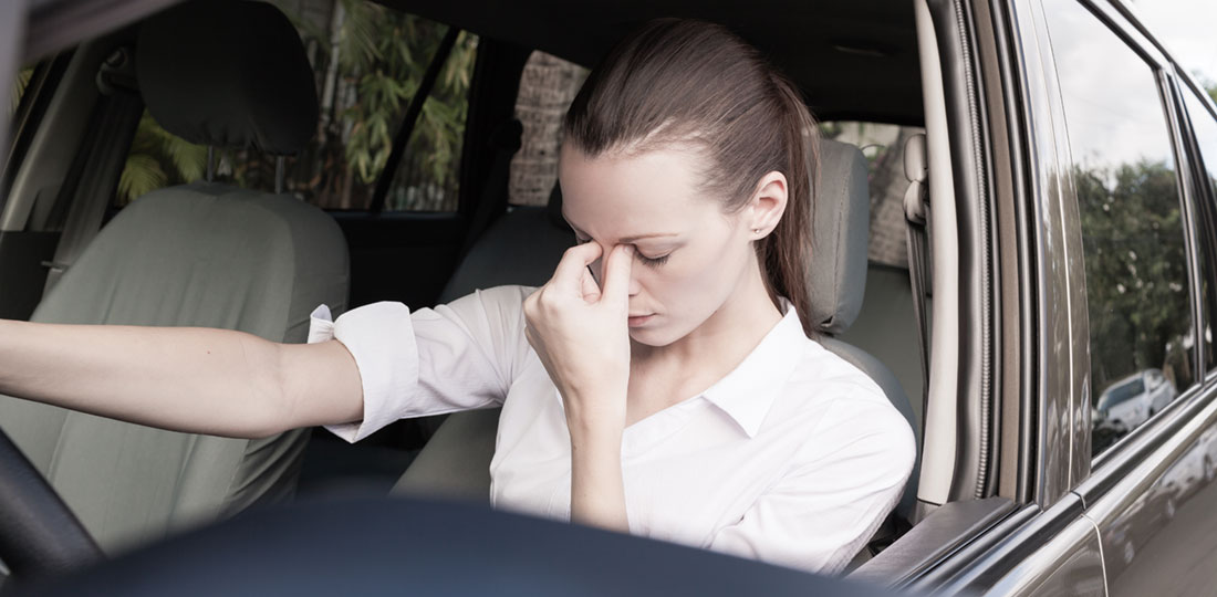 A female driver holding her index finger and thumb to her head in frustration and discomfort.
